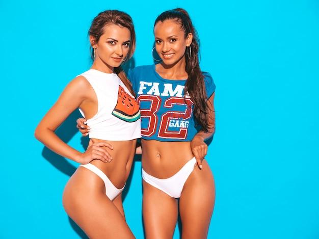 Un ritratto di due giovani belle donne sexy sorridenti in mutande ed argomento bianchi di estate. ragazze alla moda che si divertono. modelli positivi
