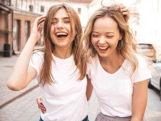Un ritratto di due giovani belle ragazze sorridenti bionde dei pantaloni a vita bassa in vestiti bianchi della maglietta dell'estate d'avanguardia. . divertirsi con i modelli positivi
