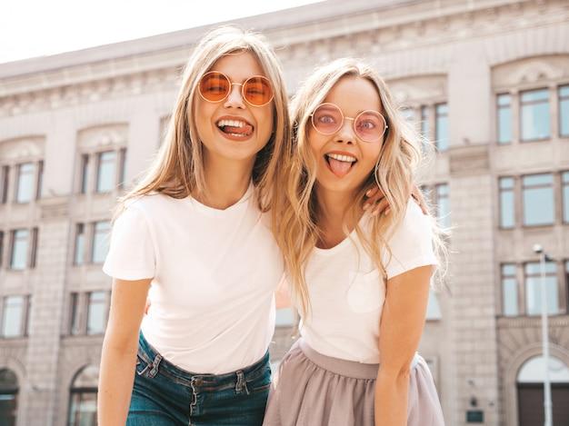 Un ritratto di due giovani belle ragazze sorridenti bionde dei pantaloni a vita bassa in vestiti bianchi della maglietta dell'estate d'avanguardia. donne spensierate sexy in posa sulla strada. modelli positivi che mostrano la lingua, in occhiali da sole