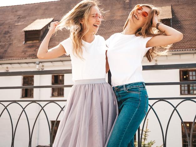 Un ritratto di due giovani belle ragazze sorridenti bionde dei pantaloni a vita bassa in vestiti bianchi della maglietta dell'estate d'avanguardia. . modelli positivi che si divertono in occhiali da sole
