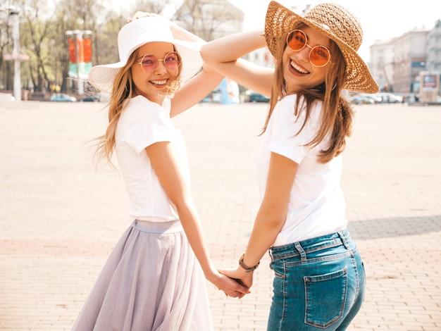 Un ritratto di due giovani belle ragazze sorridenti bionde dei pantaloni a vita bassa in vestiti bianchi della maglietta dell'estate d'avanguardia. . modelli positivi che si tengono per mano