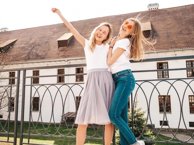 Un ritratto di due giovani belle ragazze sorridenti bionde dei pantaloni a vita bassa in vestiti bianchi della maglietta dell'estate d'avanguardia. . modelli positivi che sollevano le mani