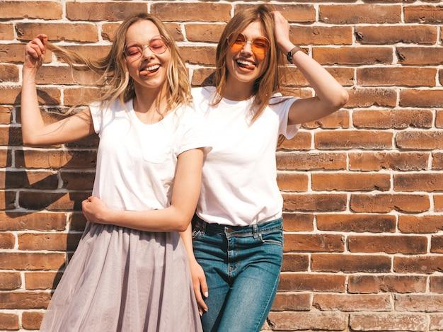 Un ritratto di due giovani belle ragazze sorridenti bionde dei pantaloni a vita bassa in vestiti bianchi della maglietta dell'estate d'avanguardia. sexy spensierato. modelli positivi che si divertono in occhiali da sole