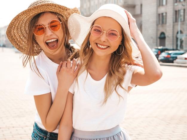 Un ritratto di due giovani belle ragazze sorridenti bionde dei pantaloni a vita bassa in vestiti bianchi della maglietta dell'estate d'avanguardia.