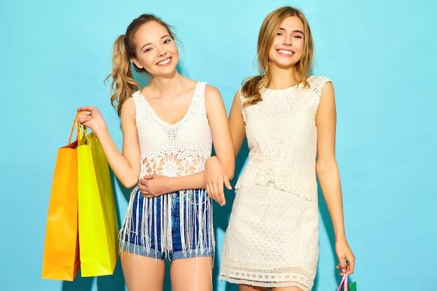 Un ritratto di due giovani donne bionde sorridenti alla moda che tengono i sacchetti della spesa. donne vestite in abiti hipster estate. modelli positivi che posano sopra il blackground blu
