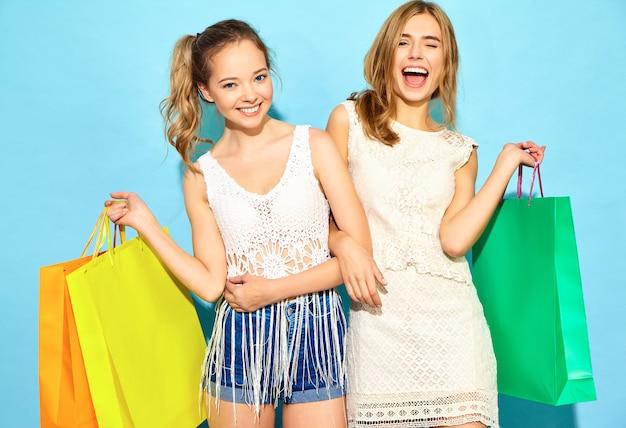 Un ritratto di due giovani donne bionde sorridenti alla moda che tengono i sacchetti della spesa. donne vestite in abiti hipster estate. modelli positivi che posano sopra la parete blu