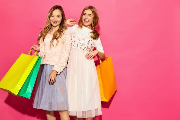Un ritratto di due giovani donne bionde sorridenti alla moda che tengono i sacchetti della spesa. donne vestite in abiti hipster estate. modelli positivi che posano sopra la parete rosa