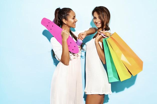 Un ritratto di due giovani donne castane sorridenti alla moda sexy che tengono i sacchetti della spesa. donne calde vestite in abiti hipster estate. modelli positivi che posano sopra la parete blu