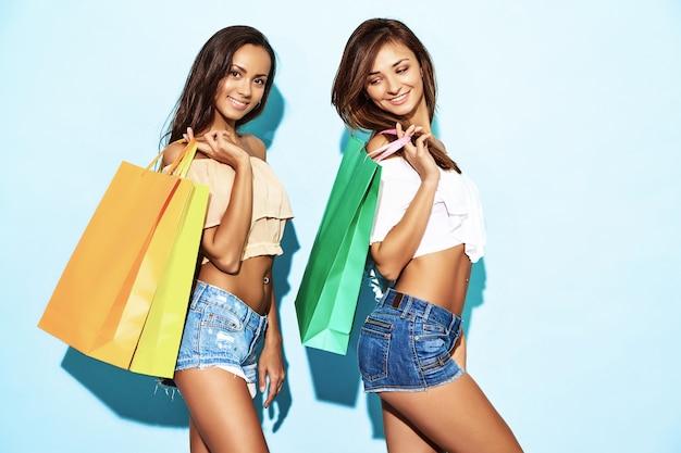 Un ritratto di due giovani donne castane sorridenti alla moda sexy che tengono i sacchetti della spesa. donne vestite in abiti hipster estate. modelli a caldo positivi che posano sopra la parete blu