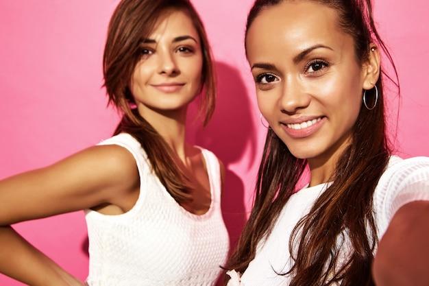 Un ritratto di due giovani donne sorridenti alla moda del brunette. donne vestite in abiti hipster estate. modelli positivi che fanno selfie sul telefono sulla parete rosa