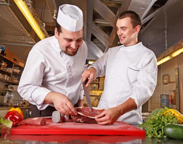 Un ritratto di due lavoratori in uniforme del cuoco che produce alimento in cucina moderna