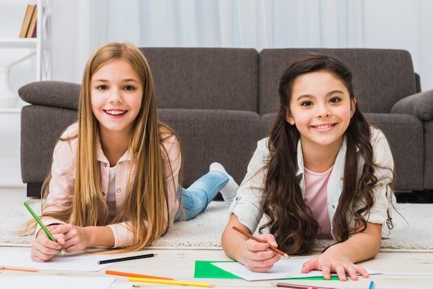 Un ritratto di due ragazze che mettono su tappeto che disegna colore con la matita che guarda alla macchina fotografica