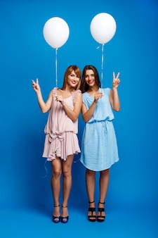 Un ritratto di due ragazze che riposano al partito sopra la parete blu