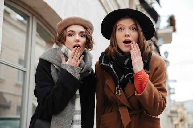 Un ritratto di due ragazze sorprese si è vestito in vestiti di autunno