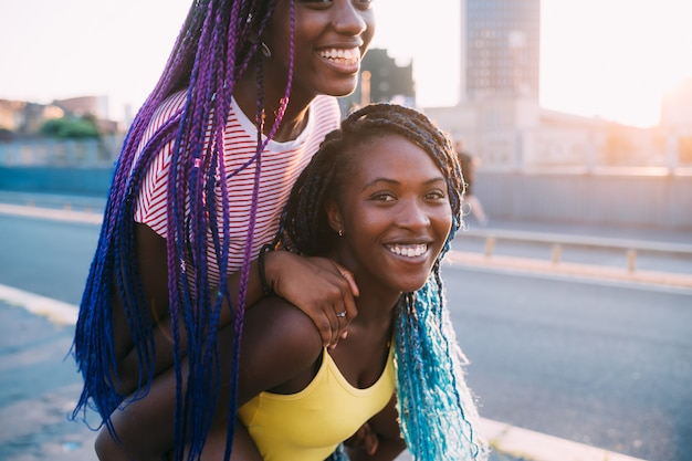 Un ritratto di due sorelle donne di colore all'aperto divertirsi abbracciando a cavallo sulle spalle