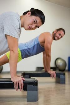 Un ritratto di due uomini che fanno esercizio aerobico su passo passo