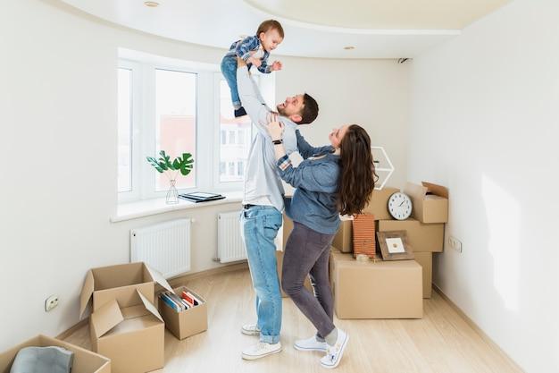 Un ritratto di giovane coppia con un bambino e scatole di cartone in movimento in una nuova casa