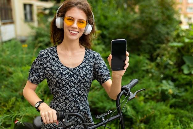 Un ritratto di giovane donna caucasica con un sorriso perfetto, labbra carnose, occhiali, auricolari, passeggiate nella natura, andare in bicicletta e mostra un telefono