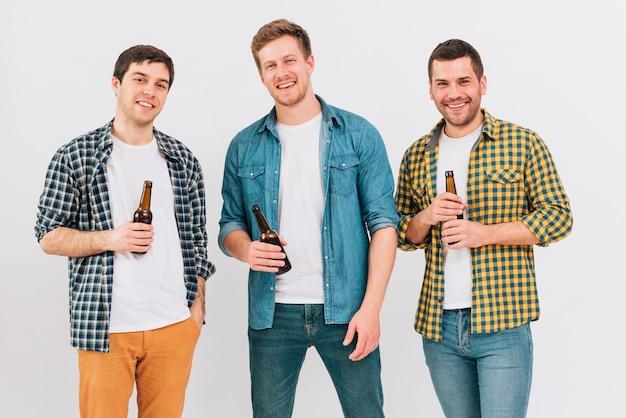 Un ritratto di tre amici sorridenti che giudicano le bottiglie di birra a disposizione che esaminano macchina fotografica