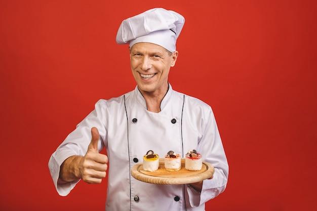 Un ritratto di un panettiere senior che giudica i dolci deliziosi isolati su fondo rosso. pollice su.