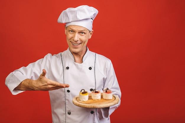 Un ritratto di un panettiere senior che giudica i dolci deliziosi isolati su fondo rosso.