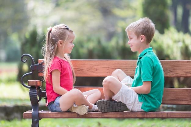 Un ritratto di un ragazzo e una ragazza di due bambini abbastanza svegli divertendosi su un banco nel parco di estate all'aperto.