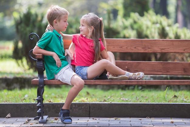 Un ritratto di un ragazzo e una ragazza di due bambini divertendosi tempo su un banco nel parco di estate.