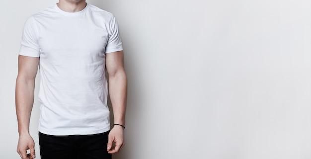 Un ritratto di un uomo che ha un corpo atletico che indossa t-shirt bianca vuota in piedi sul muro bianco con spazio di copia