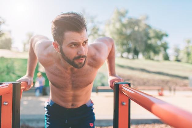 Un ritratto di un uomo muscoloso con la barba concentrato in abiti neri allenamento facendo immersioni su barre parallele. equipaggia la forma fisica con il cielo blu sullo sfondo e lo spazio aperto intorno a lui. sport e crossfit.
