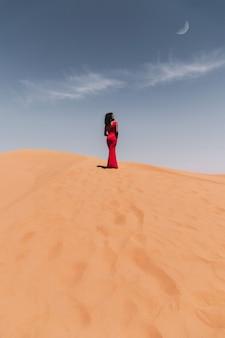 Un ritratto di una donna africana in una duna con un vestito rosso nel deserto del sahara