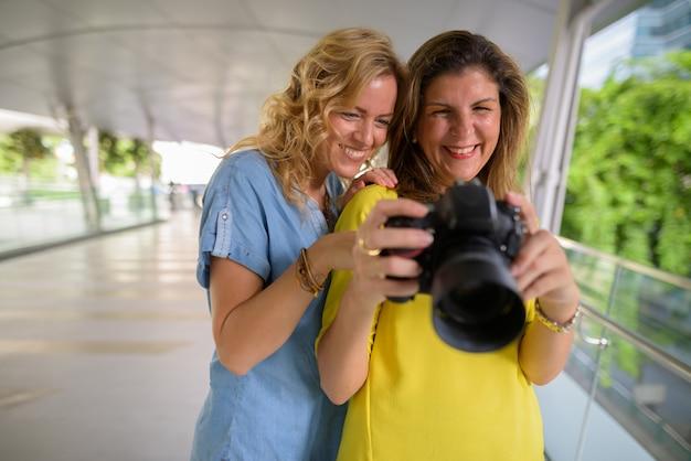 Un ritratto di una donna felice due insieme all'aperto facendo uso della macchina fotografica