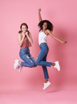 Un ritratto di una giovane donna allegra due che salta e che celebra