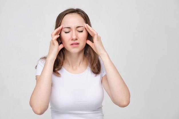 Un ritratto di una giovane donna in una camicia bianca che tiene le mani sulla sua testa. il concetto di forte dolore alla testa. mal di testa.