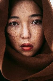 Un ritratto di una giovane donna kazaka con le lentiggini ricoperta da una coperta marrone