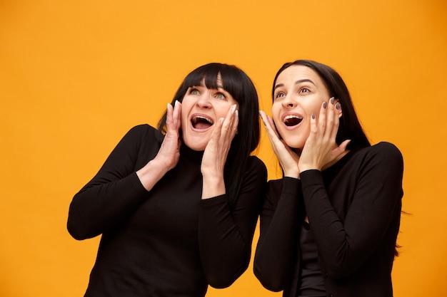 Un ritratto di una madre e una figlia sorprese in studio su fondo oro. colori alla moda. le emozioni positive umane e il concetto di espressioni facciali