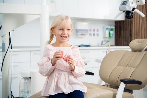 Un ritratto di una piccola paziente seduta sulla sedia del dentista con dentiere in mano e sorridente con un sorriso a trentadue denti