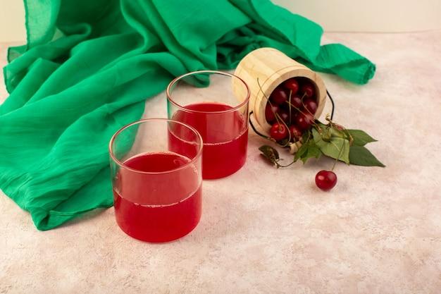 Un rosso cocktail ciliegia vista frontale all'interno di piccoli bicchieri di raffreddamento fresco insieme a ciliegie fresche sul rosa