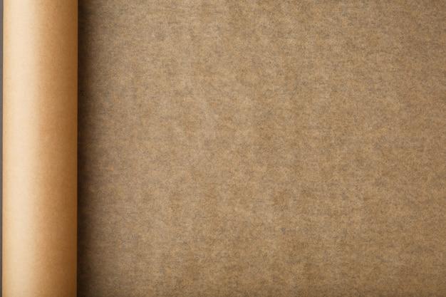 Un rotolo di carta pergamena marrone aperta, per cuocere il cibo su uno sfondo scuro, vista dall'alto.