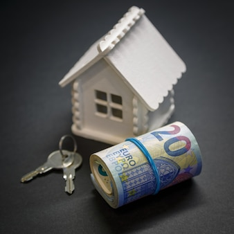 Un rotolo di euro, casa giocattolo e chiavi su fondo nero