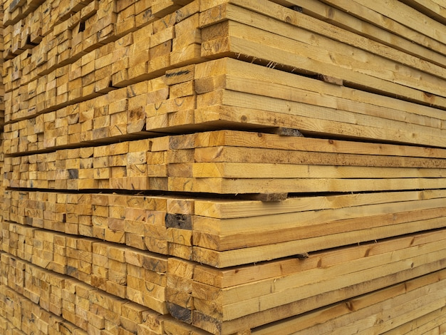 Un sacco di assi impilati uno sopra l'altro nel magazzino. legname per ulteriore utilizzo in edilizia