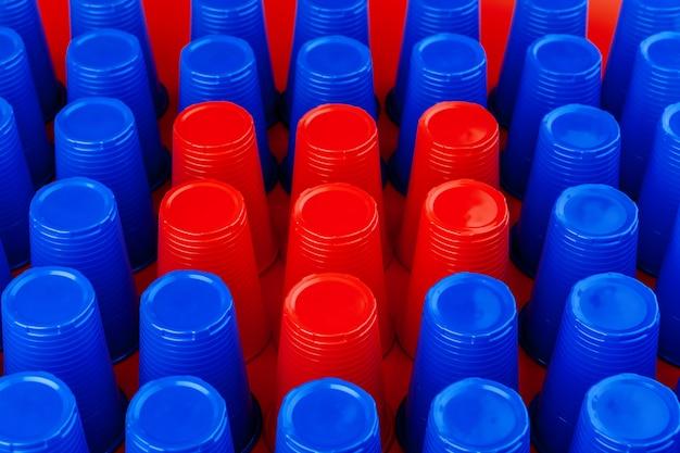 Un sacco di bicchieri colorati vuoti di plastica
