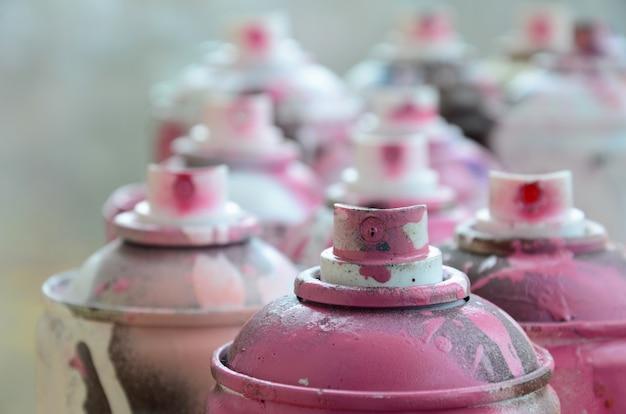 Un sacco di bombolette aerosol sporche e usate di vernice rosa brillante. macro fotografia con profondità di campo.