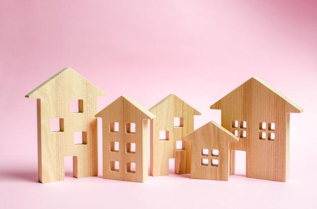 Un sacco di case in legno su uno sfondo rosa.