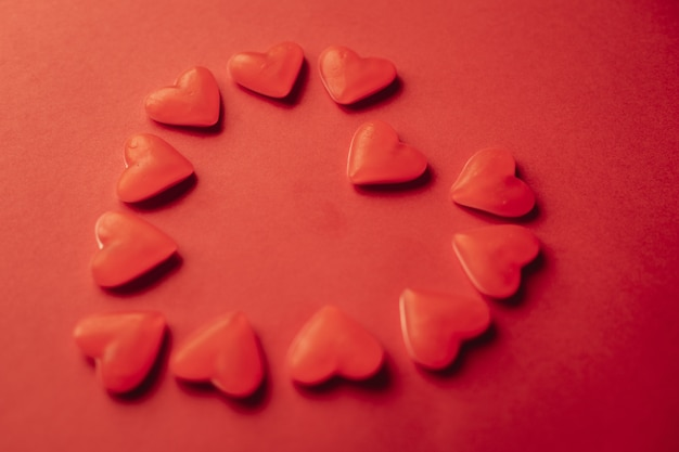 Un sacco di cuori gommosi che formano la forma di un cuore gigante in rosso con sfondo rosso
