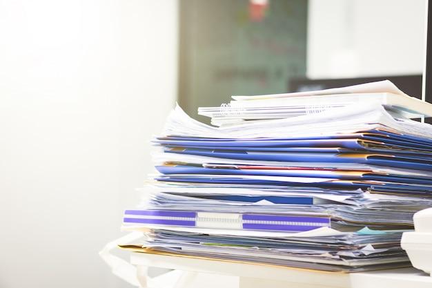 Un sacco di documenti non finiti sulla scrivania. mucchio di documenti in carta.