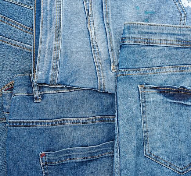 Un sacco di jeans classici blu accatastati in modo caotico, tasca posteriore