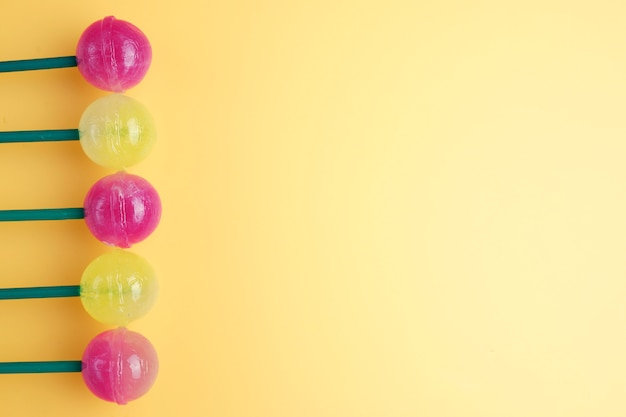 Un sacco di lecca-lecca colorfull a sinistra. lecca-lecca su sfondo giallo. copia spazio per il testo.