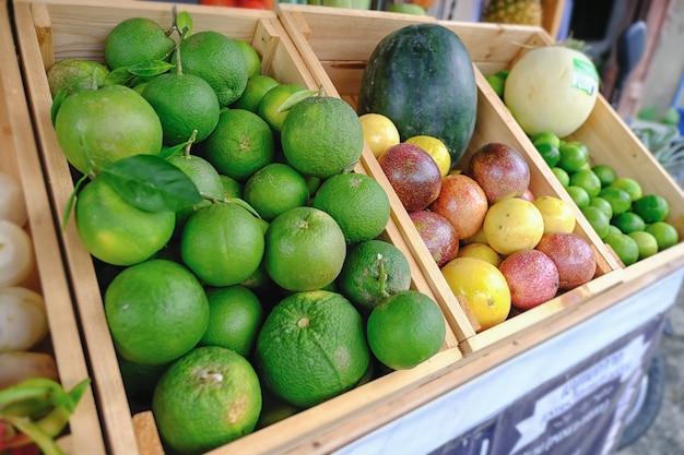 Un sacco di mandarino e molti frutti misti in un cestino di legno per capelli.