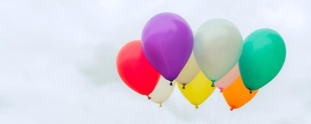 Un sacco di palloncini colorati sul cielo blu, concetto di amore in estate e san valentino, luna di miele matrimonio - banner panoramico. immagini di stile d'effetto vintage.
