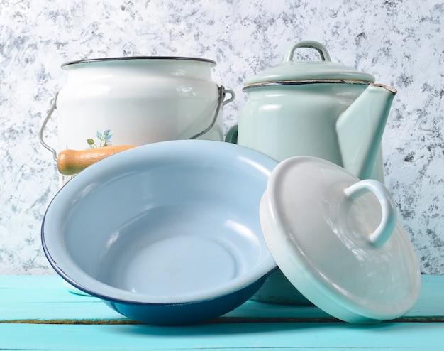 Un sacco di piatti smaltati su un tavolo blu su uno sfondo bianco muro di cemento. pentole in stile retrò